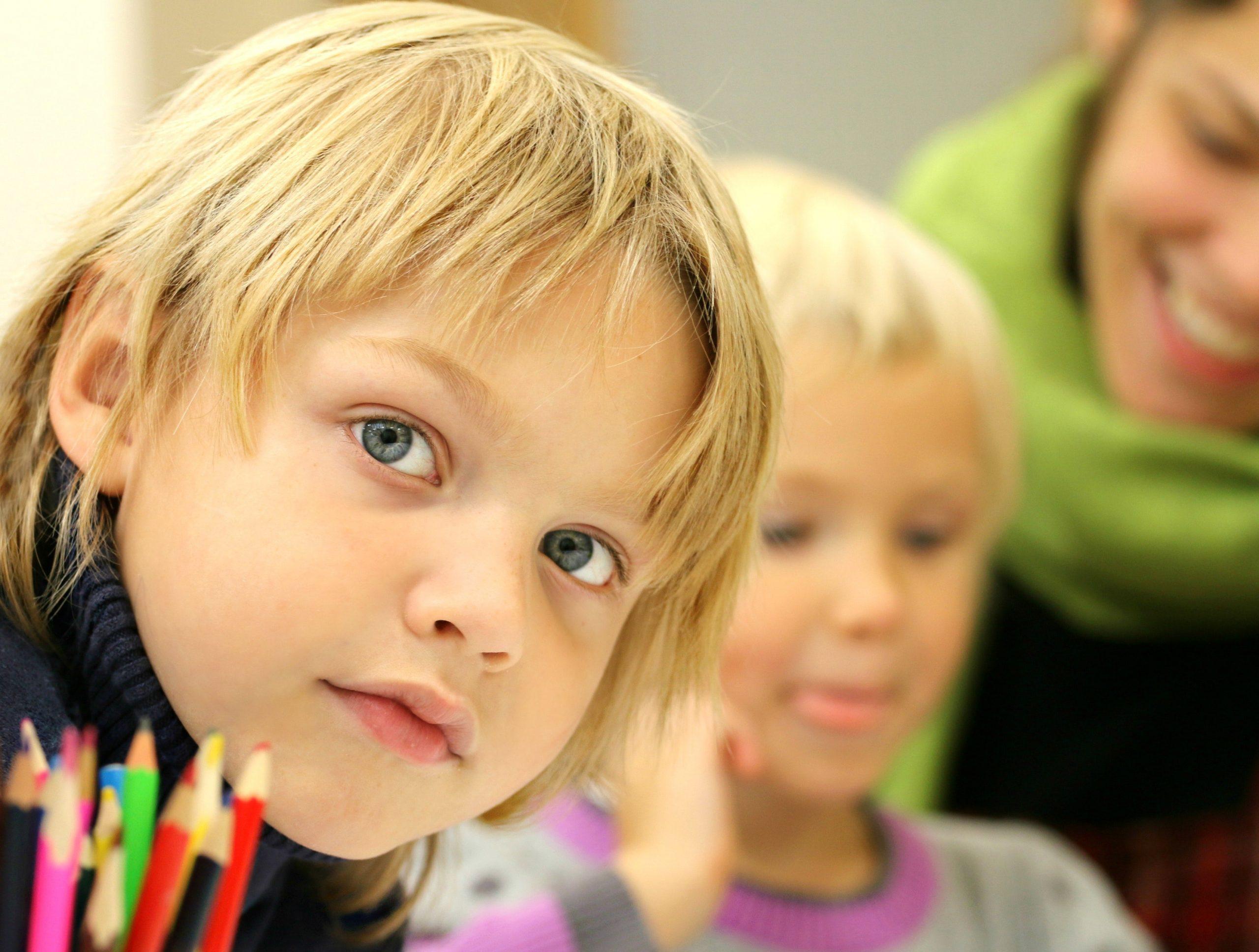 boy staring at camera with pencils
