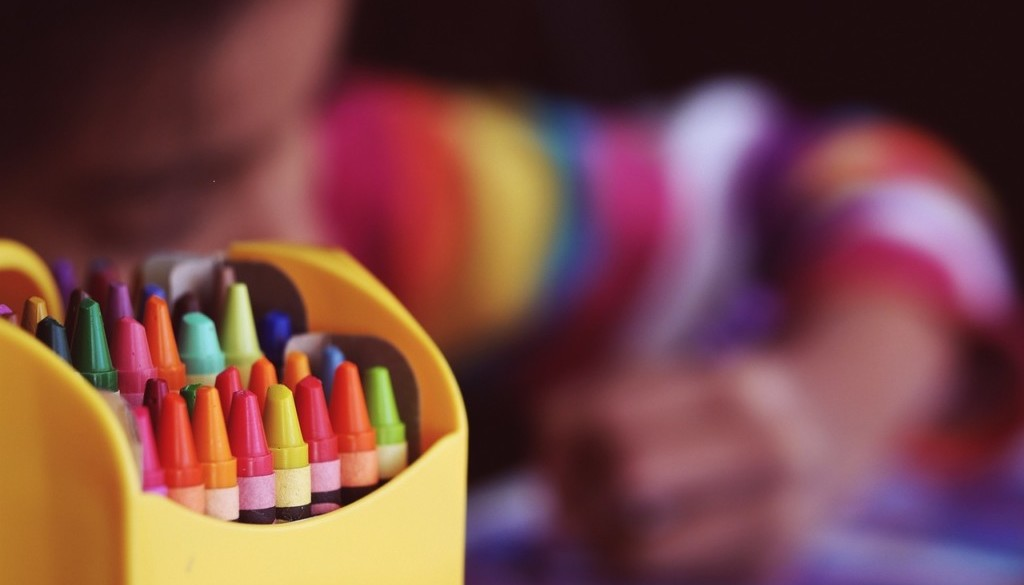 Crayons with child blurred in background